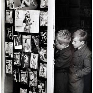 Two boys peer through the window of McDonalds the newsagent.